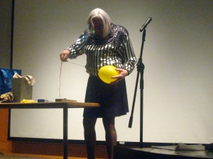 Mary Magician sticks a needle through a balloon without breaking it.