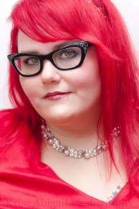 Photo: Jamie Royce headshot, a fat white women with bright red hair and black cat eye glasses. Image source: Google Images, Kriss Abigail Photography