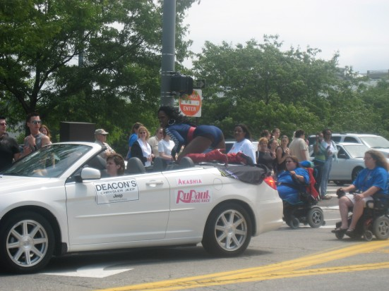 Akashia from RuPaul's Drag Race gets down atop of a convertible during the parade.