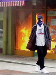 Photo: During the Cincinnati race riots, a fire burns in a store front as a black man walks away with a bandana over his face. Photo Source: Cincinnati Enquirer, Google Images