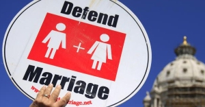 "Photo: A white hand holding up a white sign that reads ""defend marriage"" with man and woman bathroom gender symbols underneath. Photo source: Google Images minn-GAY-marriage-ban"