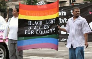 "A black woman and a black man hold a rainbow flag with a black panel in the middle that reads, ""Black LGBT and allies for equality."" Photo source: GayLiberation.net via Google Images"