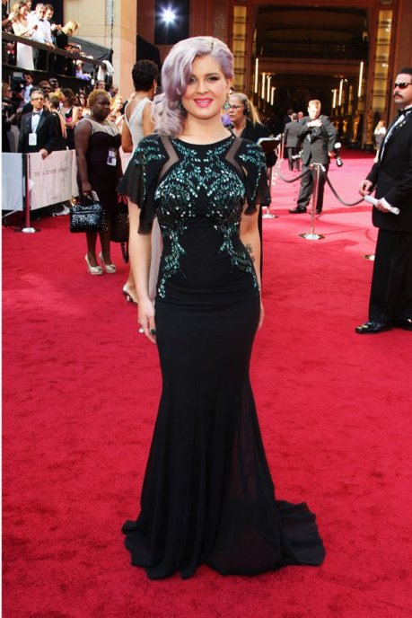 Photo: Kelly Osbourn in a form-fitting long black Badgley Mischka gown with emerald green beading and gems. She has light lavender hair. Image source: Photo By Gregg DeGuire/WireImage, Google Images