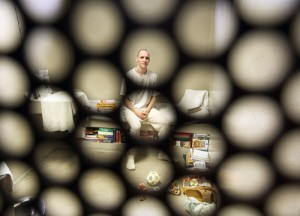 Photo: Tiny clear circles, the view from outside the cell, cover a white man sitting in a prison cell at Tamms in Illinois. Photo source: Tribune, Google Images