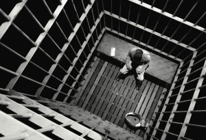 Photo: A black and white view of the inside of a cage cell with a white man in a prison jumpsuit sitting on a bench with only a toilet inside. Photo source: Google Images