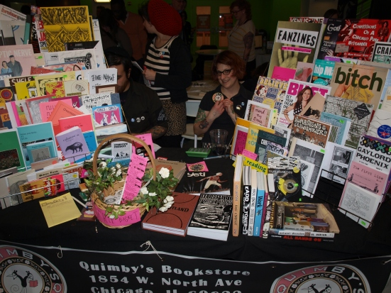 Photo: Liz Mason, a white feminine woman, sits behind a table filled with zines and other publications from Quimby's Bookstore. Google Images