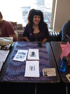 "Photo: Rosy Phinick, a white woman with a dark bouffant, showcases her zines ""Bacterial Turned Viral"" at a table at Chicago Zine Fest. Google Images"