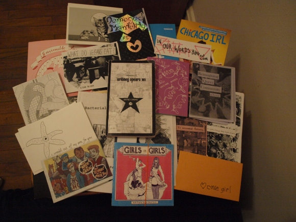 Photo: Chicago Zine Fest Haul. Various zines, about 20 of them, laid out on a table. Google Images.