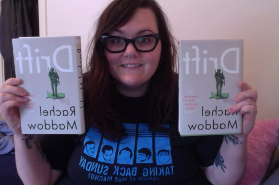 "Photo: Me, a white woman with long dark hair and big, black glasses, holding two copies of ""Drift,"" Rachel Maddow's new book. Google Images."