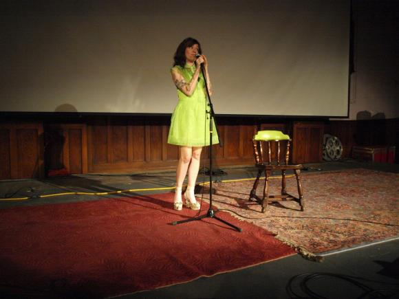 Photo: Michelle Tea, a white woman with long hair, emceeing the show in a flowy lime green dress. Google Images.