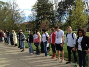 Photo: Miami University community members hold hands at the rally in response to the hate crime. Photo source: The Miami Student, Google Images