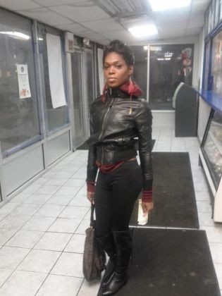 Photo: A full body photo of Paige Clay, a younger black woman wearing a black leather jacket and black pants. Photo source: Brian Turner, Examiner.com, Google Images