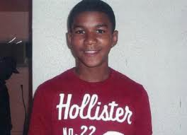 Photo: Head shot of Trayvon Martin, a young black man with short hair wearing a red T-shirt. Photo source: Google Images