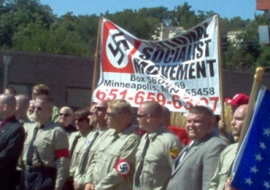 Photo: A group of white men wearing Nazi military uniforms with swastikas hold a National Social Movement banner during a protest rally. Photo source: Google Images