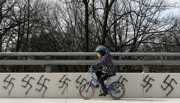 Photo: A white girl child rides on a bicycle past as row of swastikas spraypainted on an overpass in Clintonville, Ohio. Photo source: The Columbus Dispatch, Google Images