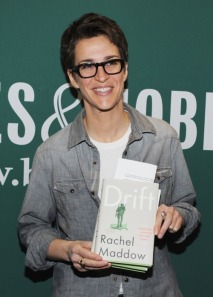 "Photo: Rachel Maddow, a white masculine woman with short dark hair and big, black glasses, holding a copy of her new book ""Drift: The Unmooring of American Military Power."" Photo source: AfterEllen, Google Images"