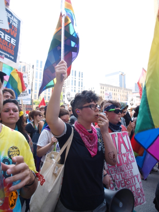 Photo: A protestor holds a rainbow flag and speaks into a bullhorn while marching with the queer contingent of the NATO Summit protests.