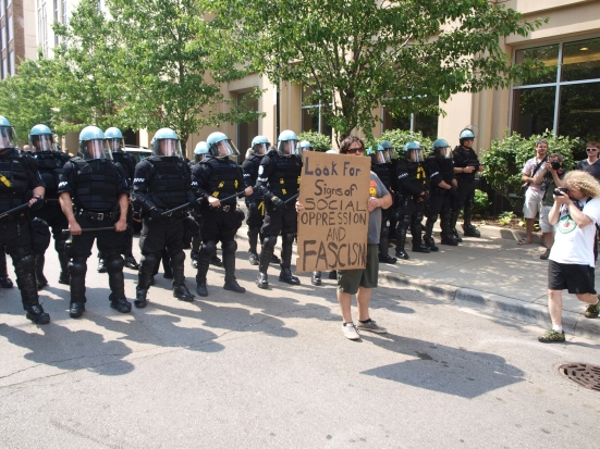 "Photo: A wall of Chicago Police in riot gear with a white man standing in front holding a sign that reads: ""Look for signs of social oppression and fascism."""