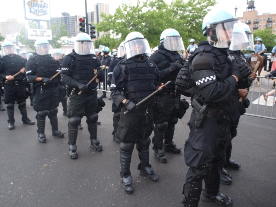Photo: Police lined up in riot gear holding batons in their hands at the Chicago protests of the NATO Summit.