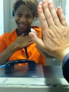 Photo: CeCe McDonald, a black woman, wearing an orange jumpsuit while having a prison visit with Leslie Feinberg. Feinberg's hand is touching CeCe's through the glass. Photo source: Leslie Feinberg, Google Images.