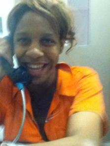 Photo: CeCe McDonald, a black woman, wearing an orange jumpsuit talking into a phone behind bulletproof glass. Photo source: Leslie Feinberg, Google Images