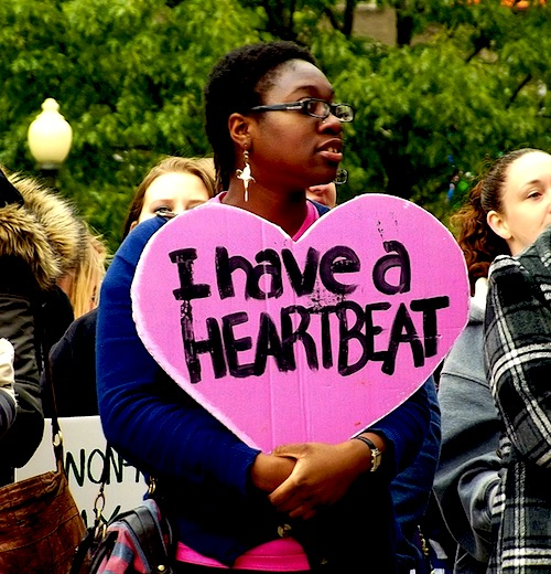 "Photo: A black woman at a protest holding a pink heart-shaped sign reading ""I have a heartbeat"" in protest of Ohio's abortion-limiting ""heartbeat bill."" Photo source: Google Images"