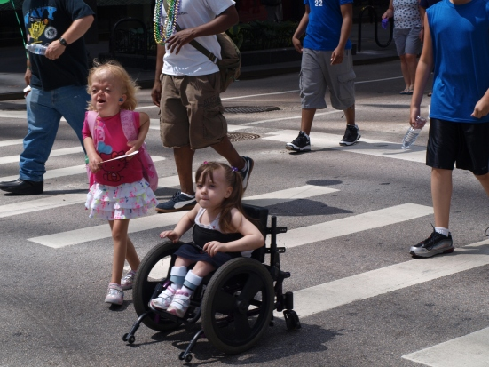 Photo: Disability Pride Chicago: Two white feminine children participate in the parade, one of which is in a wheelchair.