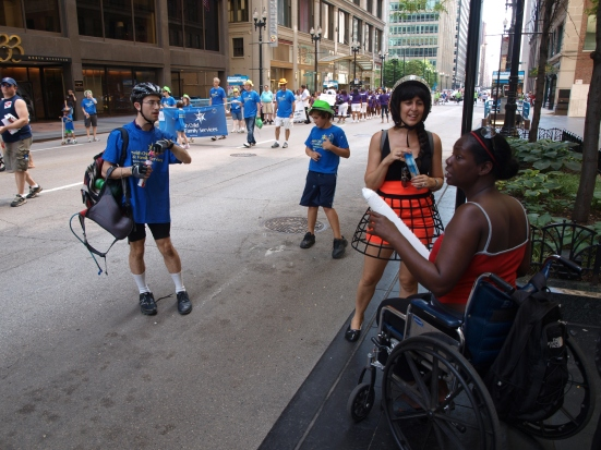 Photo: Disability Pride Chicago: Parade participants speak with audience members. Google Images.