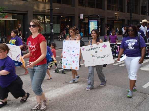 "Photo: Disability Pride Chicago. Parade participants that read, ""We're here united. We won't be divided,"" and ""Disability is not inability."" Google Images."