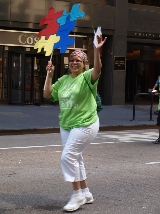 Photo: Disability Pride Chicago: A black woman holds an autism awareness puzzle piece sign. Google Images