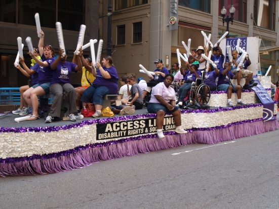 Photo: Disability Pride Chicago. Members of Access Living bang together noisemakers on a float in the parade. Google Images