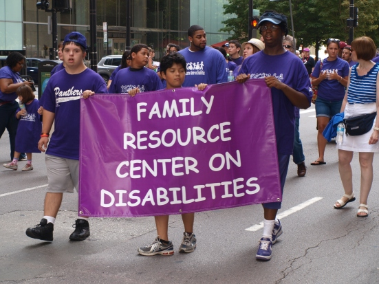 "Photo: Disability Pride Chicago: People in purple T-shirts hold a purple banner that reads ""Family Resource Center on Disabilities."""
