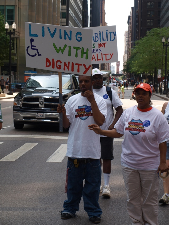 "Photo: Disability Pride Chicago. A member of the ACLU holds a sign that reads, ""Living with Dignity,"" and it has the wheelchair symbol on it. Google Images."