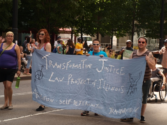 "Photo: Disability Pride Chicago: Members of Transformative Justice Law Project hold a banner that reads, ""Transformative Justice Law Project of Illinois: abolition, self-determination, transformation."" Google Images"
