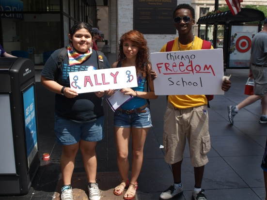 "Photo: Disability Pride Chicago. Parade participants hold signs that read, ""Chicago Freedom School"" and ""Ally"" with the wheelchair symbol. Google Images."