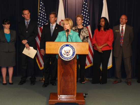 Photo: Rep. Judy Biggert, a white woman from Illinois, addresses the press room from a podium with the Congressional seal surrounded by anti-violence advocates and Rep. Robert Dold. Google Images.