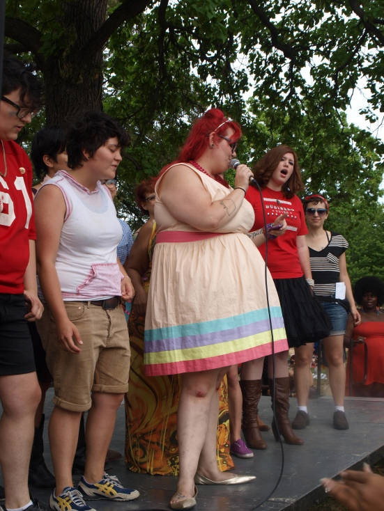 Photo: Chicago Transgender Pride (TGIF) A white woman wearing a rainbow dress with red hair reads into a microphone. Google Images.