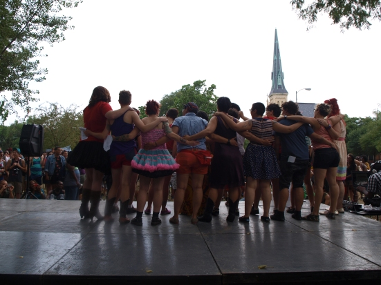 Photo: Chicago Trans Pride TGIF A group of people on stage put their arms around each other in a row. Google Images transgender