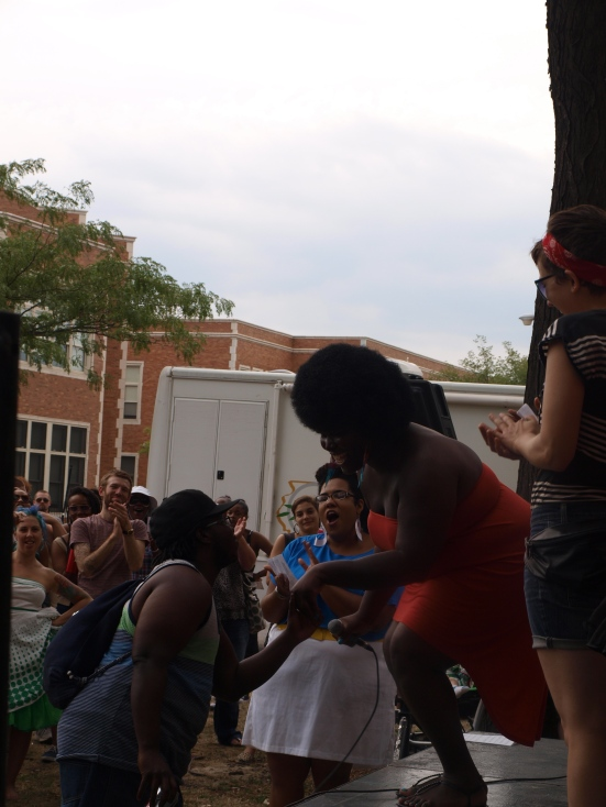 """Photo: Chicago Trans Pride TGIF Transgender Pride organizer Kokumo Kinetic, a black woman wearing an orange dress sings """"I'm Every Woman"""" backed up by Queer Choir. Google Images"""